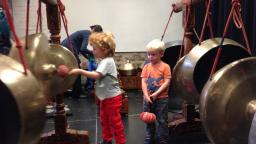 Two small children playing Gamelan (large percussion instruments)