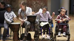 woman and three disabled children playing drums