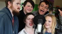 Group of young people gathered around a microphone