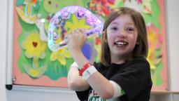 Young person wearing hospital bracelet holding tambourine