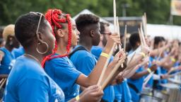 young musicians wearing blue tshirts drumming