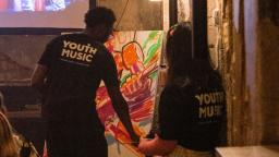 Two people with their backs to the camera wearing Youth Music tshirts. One is painting on a canvas