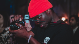 Young person taking a photo wearing a red hat and Youth Music t-shirt