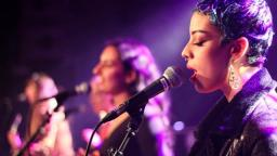 young musician singing into microphone with purple lighting