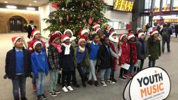 Group of children near Christmas tree behind Youth Music banner