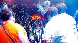 Two male musicians performing to a crowd. The image is slightly distorted effect, to make it look like double vision.