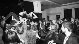 black and white photo of a live performance, where a male musician is crowd surfing