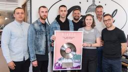 7 people standing in a row, some holding up a framed Vinyl
