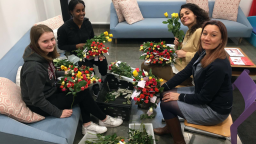 Group of four people holding bunches of roses