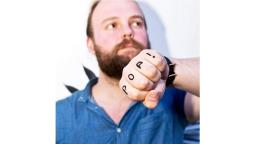 Male with beard holding his fist to the camera, with the words POP! written on his knuckles.