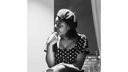 Black and white photo of a woman at a side profile, wearing a beret and a polka dot dress.