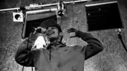 Black and white photo of person wearing a hoodie and black cap, mcing into a mic