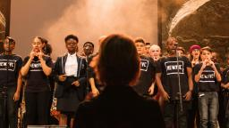 Group of young people singing on stage with conductor in foreground