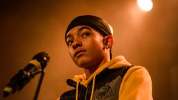 Young person wearing a yellow hoodie and black durag.