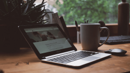 photo of an open macbook and mug on a wooden desk in front of a window