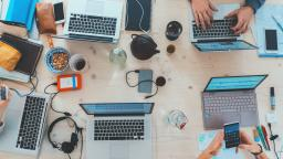 A birds eye view of a working space with hands typing on laptops on a desk, surrounded by notebooks, hard drives, and beverages.