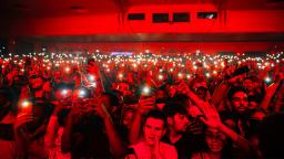 crowd in a music venue all holding their phones lights in the air, bathed in a red light.