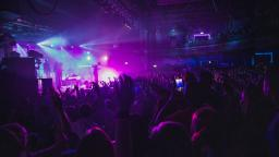 shot of a band playing live, crowd of people with hands in the air, purple and blue lights coming from the stage