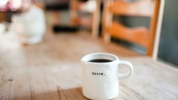 """A coffee table with a mug of black coffee, with """"Begin"""" written on the mug."""