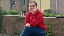 young person sitting outside with houses behind them, wearing blue jeans and a red hoodie