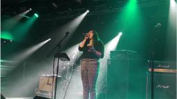 young woman on stage singing into microphone under green lights