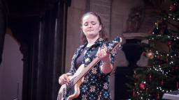 young woman with brown hair in pony tail playing a bass guitar. Christmas tree visible in right side of photo.
