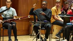 Musicians playing bassoon and tuned percussion, others looking on