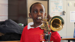Young musician playing brass instrument with one hand