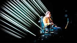 person in wheelchair against black background with white lines on it