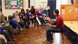 a person sitting down with a guitar, playing in front of a crowd of children and parents in a school classroom
