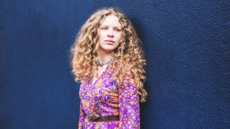 Image of Becca James. She has long curly hair, is wearing a purple, orange and pink floral dress, and is standing against a dark blue wall.