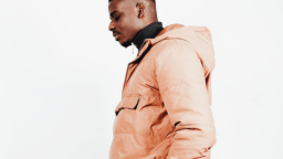 Image of Dami Sule. He is standing to the side, and wearing a beige hooded jacket over a black polo neck jumper.