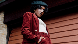 Image of Lavz. She is wearing a red two-piece suit, a white t-shirt, and a black beret.