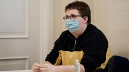 young person wearing a face mask sitting down at a table in a room.