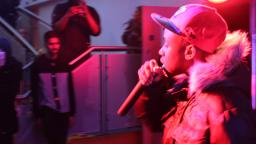 young person wearing a coat and cap rapping into a microphone, bathed in a red light