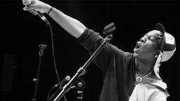 black and white photo of young person on stage pointing a microphone into the air