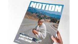 photo of a hand holding Notion Magazine, a women kneeling down on a road is on thefront cover