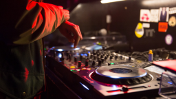 Image of a person DJ-ing. The image is a close up of their hand and the production equipment.