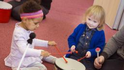 two young children banging a drum