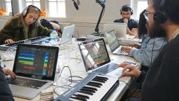 young people sat around a table with laptops and a keyboard making music
