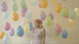 young woman standing against a wall filled with pastel coloured balloons