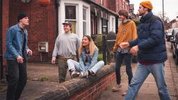 young woman sitting on a low brick wall with four other people standing nearby