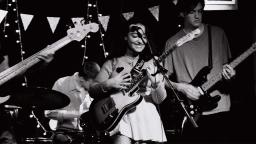 black and white photo of a woman playing guitar on stage with a band