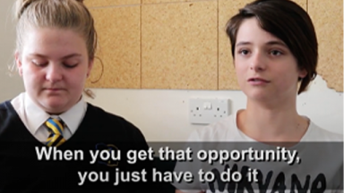 two teenagers in school uniforms with a caption at the bottom third of the screen