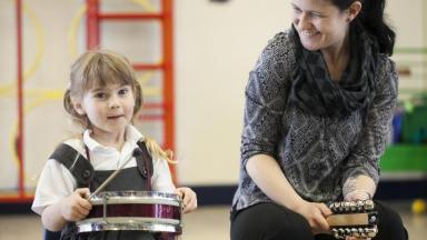young musician playing the drums smiling with a music leader smiling at her