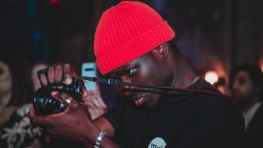 Photographer wearing red hat and Youth Music t-shirt