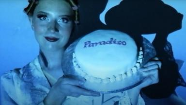 person standing against a wall in blue light holding a cake that says Paradiso.