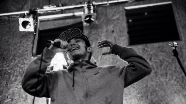 Black and white photo of person wearing a hoodie and black cap, rapping into a mic