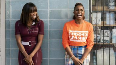 Two black people standing and laughing. One is wearing a burgundy dress, the other is wearing a orange jumper and patterned trousers.