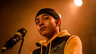 Young person wearing a yellow hoodie and a black durag